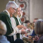 Piispa jakaa ehtoollista avustajiensa kanssa