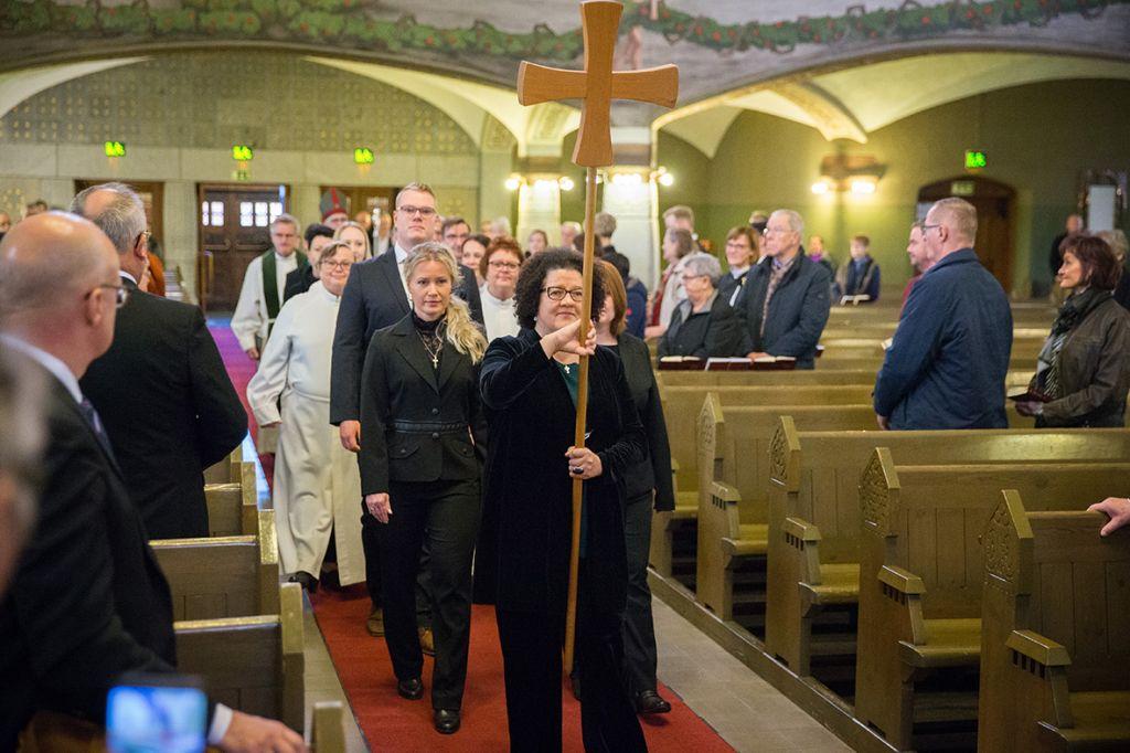 Ristikulkue kävelee kirkon keskikäytävää