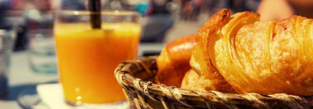 Lasillinen tuoremehua ja korissa oleva croissant