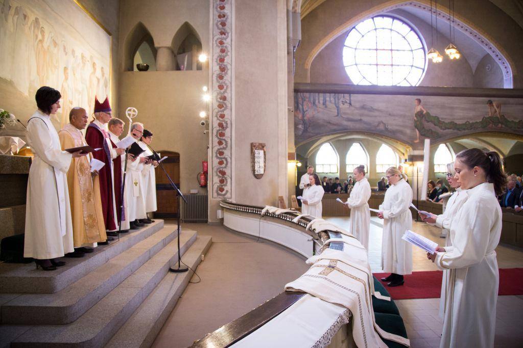 Pappis- ja diakonian virkaan vihkiminen alkamassa. Vihittävät seisovat alttarin edessä, piispa ja vihkimyksessä avustavat vierellään.