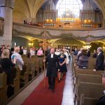 Ristikulkue astuu kirkon keskikäytävää