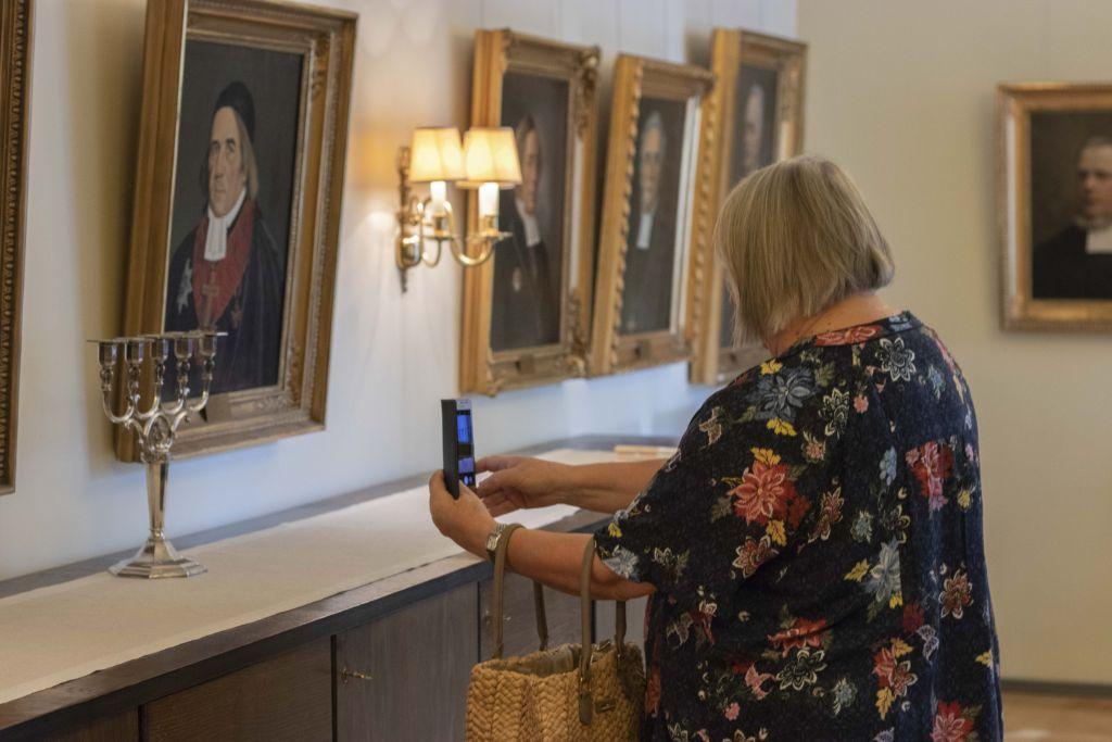Nainen ottaa kuvaa piispan muotokuvasta kännykkäkamerallaan.