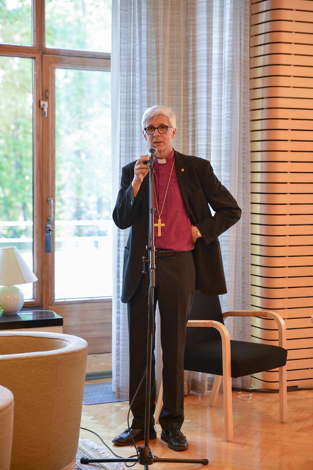 Matti Repo puhuu mikrofoniin piispantalon ikkunan edessä.