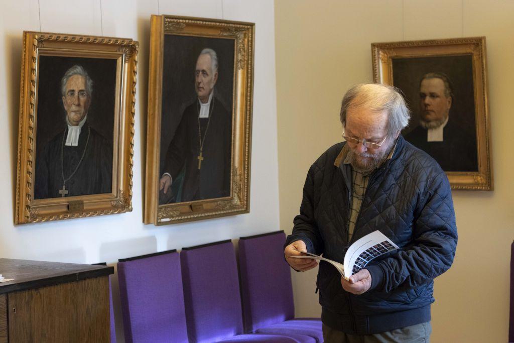 Mies tutkii paperista esitettä piispojen muotokuvien edessä.