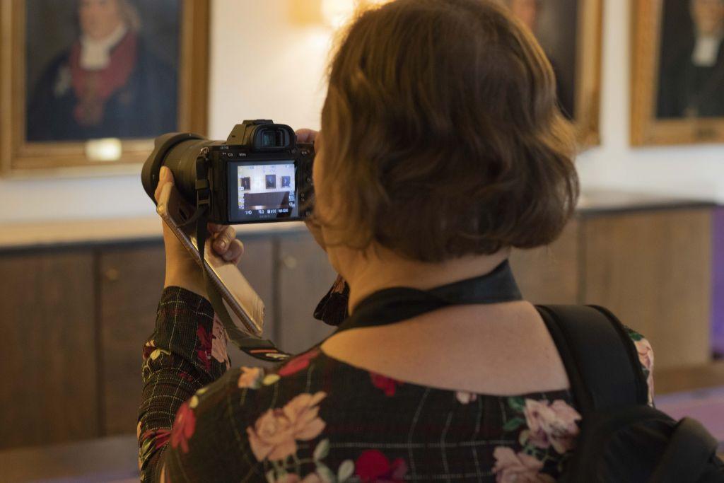 Nainen kuvattuna takaapäin katsomassa kameran linssiin.