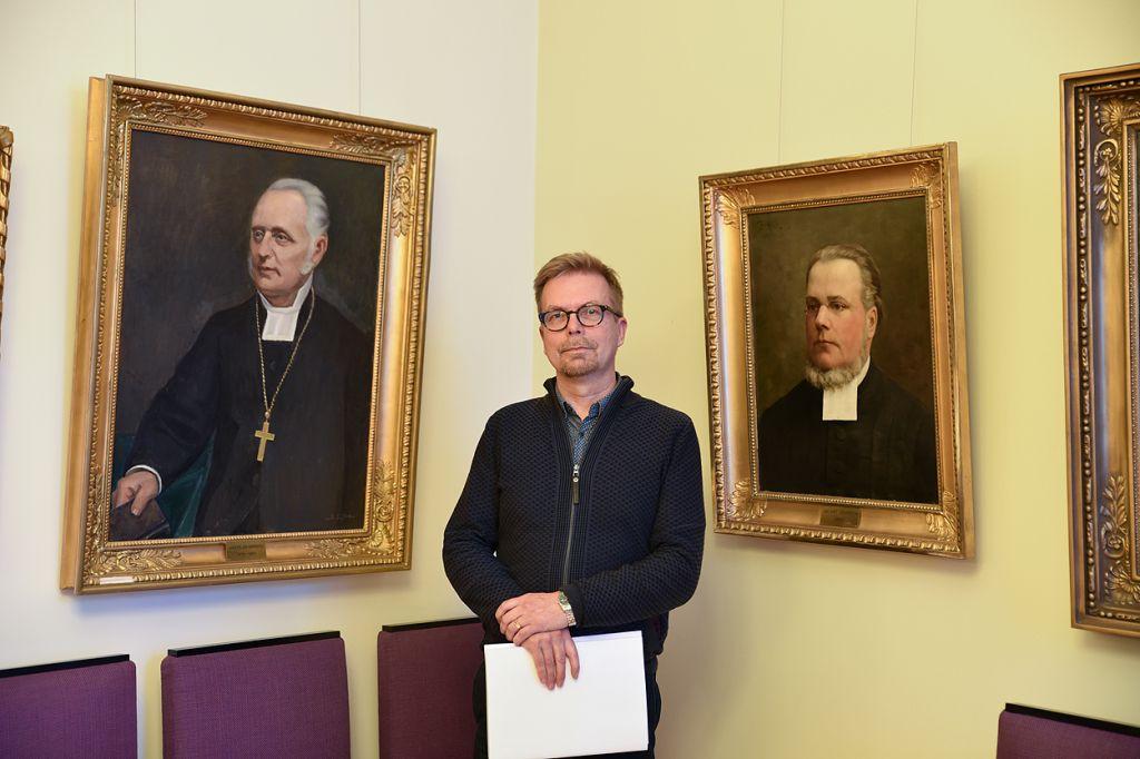 Ari Luomajoki seisoo kahden piispan muotokuvan välissä katse suunnattuna kameraan.