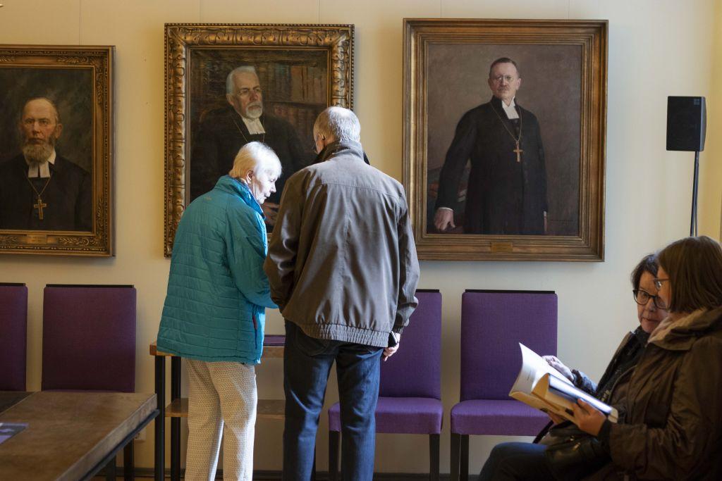Vanhempi rouva ja herra keskustelevat piispojen muotokuvien edessä.