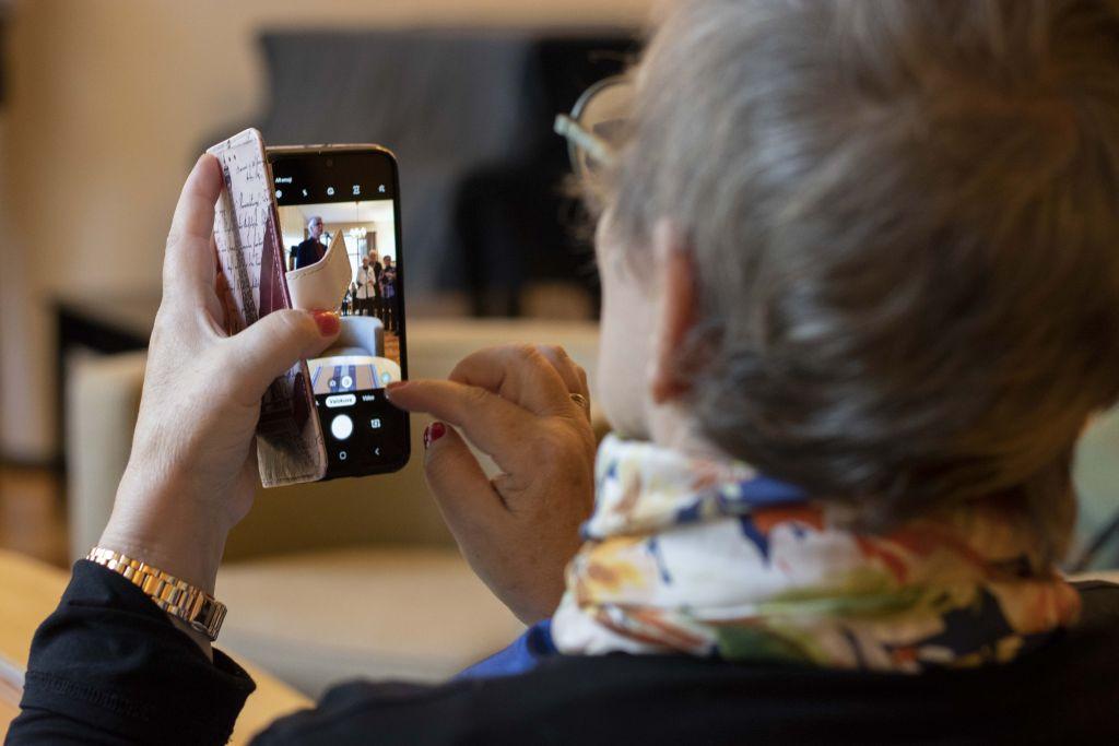 Nainen katsoo kännykkäkameraan, jonka näytöllä kuvastuu juuri otettu kuva piispasta puhumassa mikrofoniin.