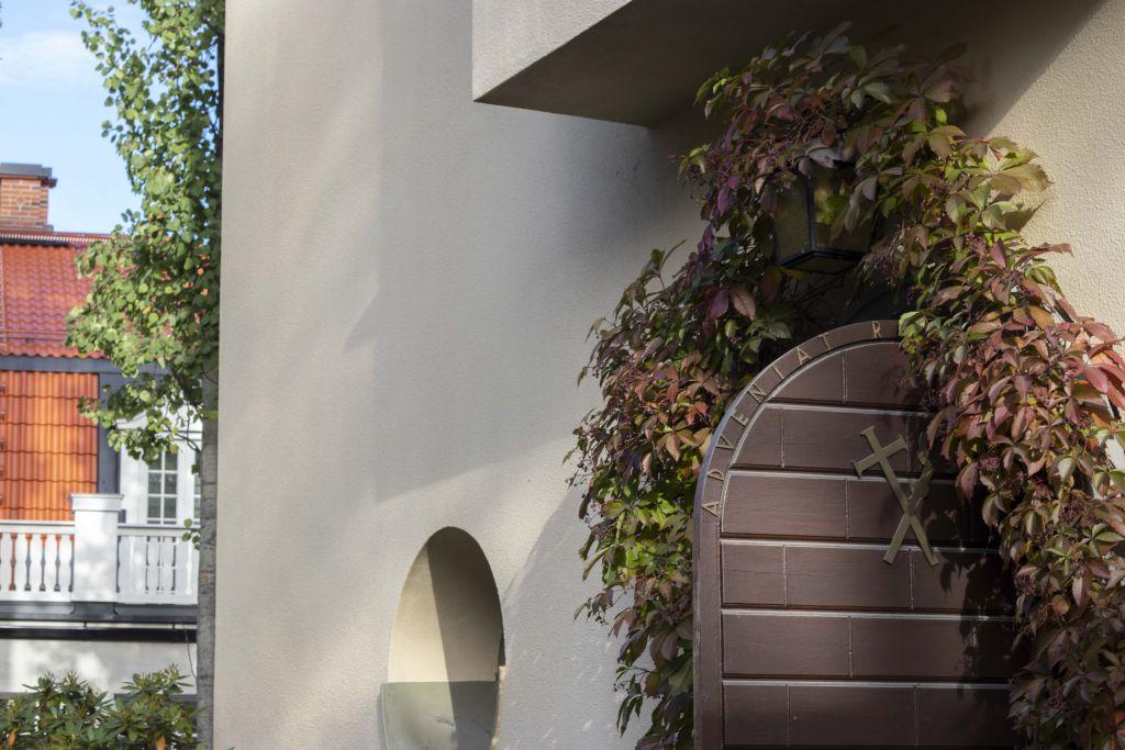Piispantalon ulko-ovi. Ovi on avoinna ja sitä kehystää villiviini.