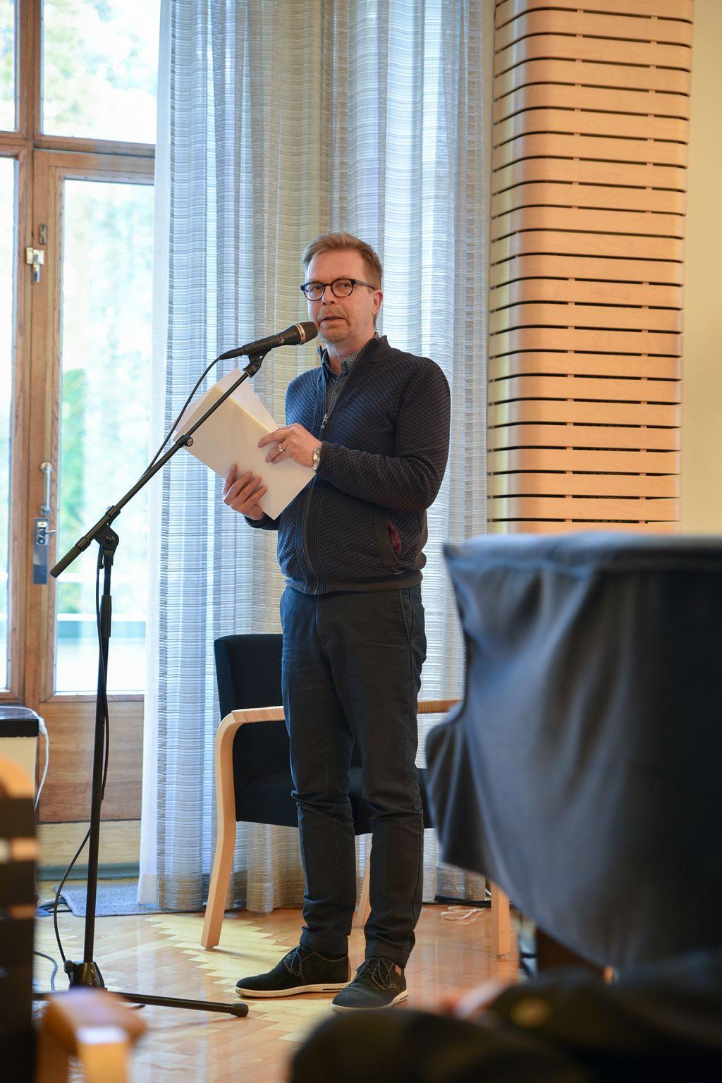 Ari Luomajoki pitää esitelmää ja seisoo flyygelin edessä nippu paperia kohotettuna edessään.