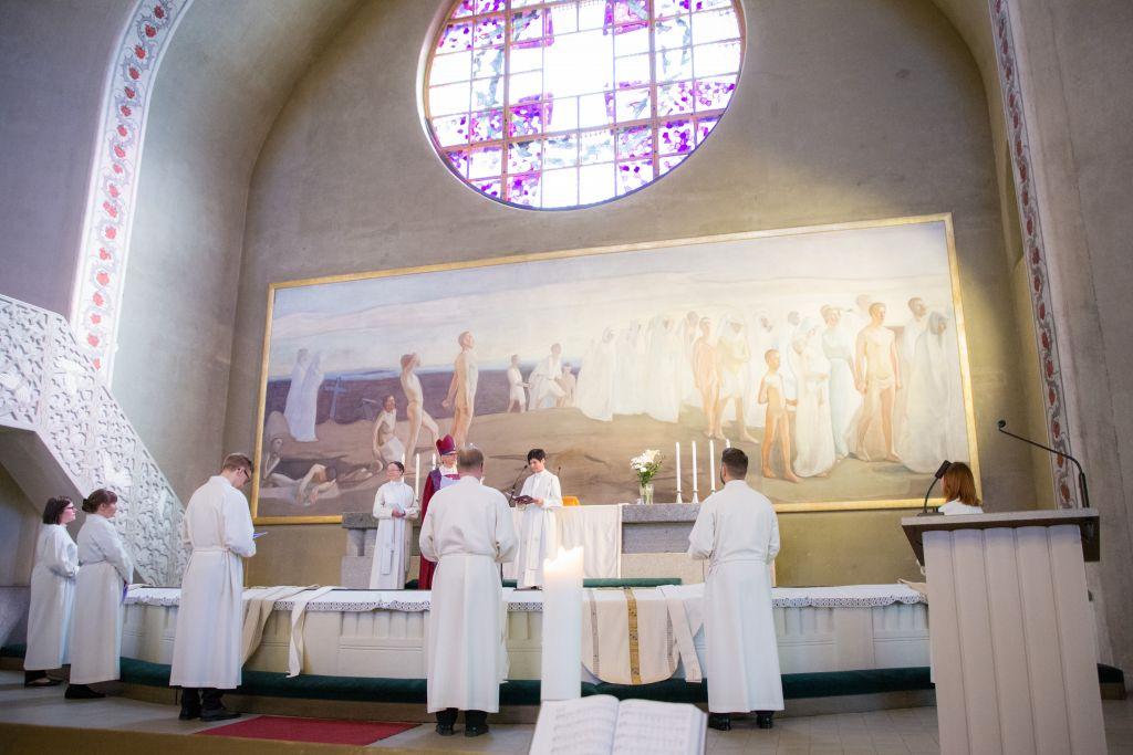 Papiksi ja diakoneiksi vihittävät seisovat alttarin edessä ja katsovat alttarilla seisoviin vihkimyksen toimittajiin.