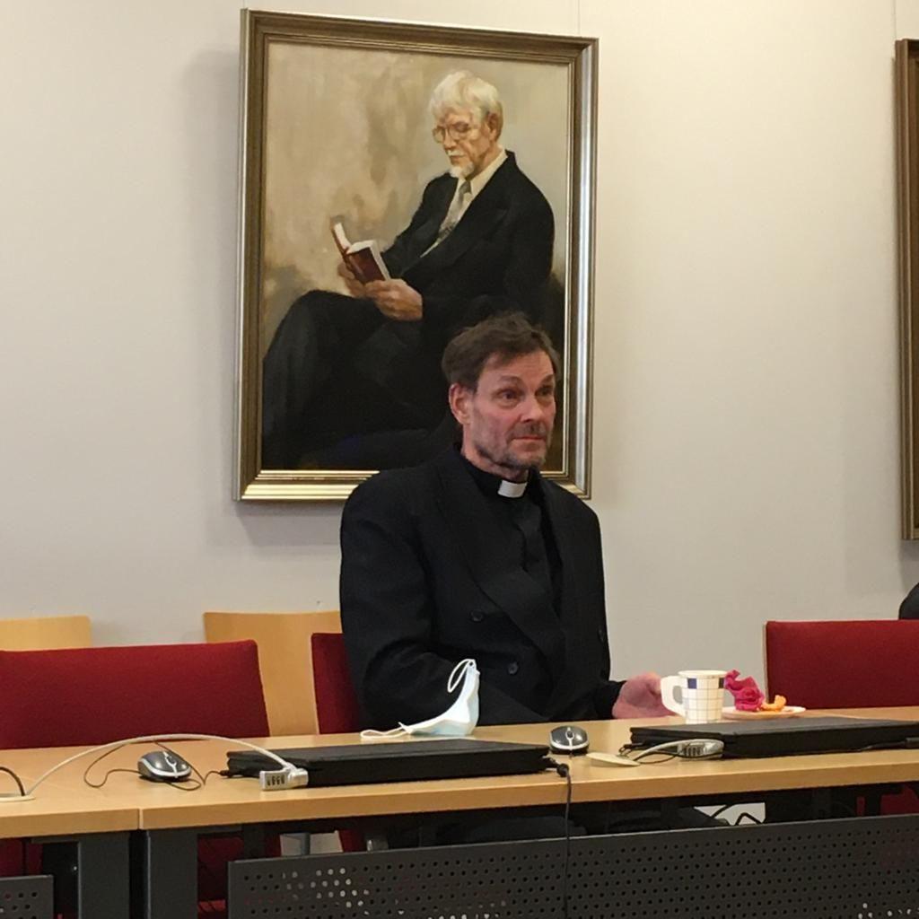 Johannes Riuttala istuu pöydän ääressä, takanaan vanha muotokuva.