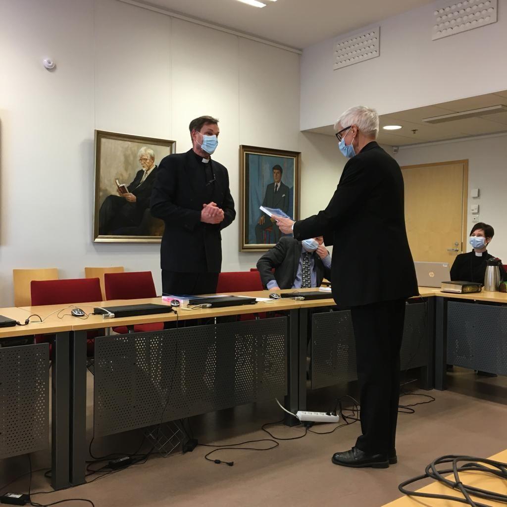 Piispa ojentaa Riuttalalle tämän todistuksen. Molemmilla on kasvoillaan suojamaski.
