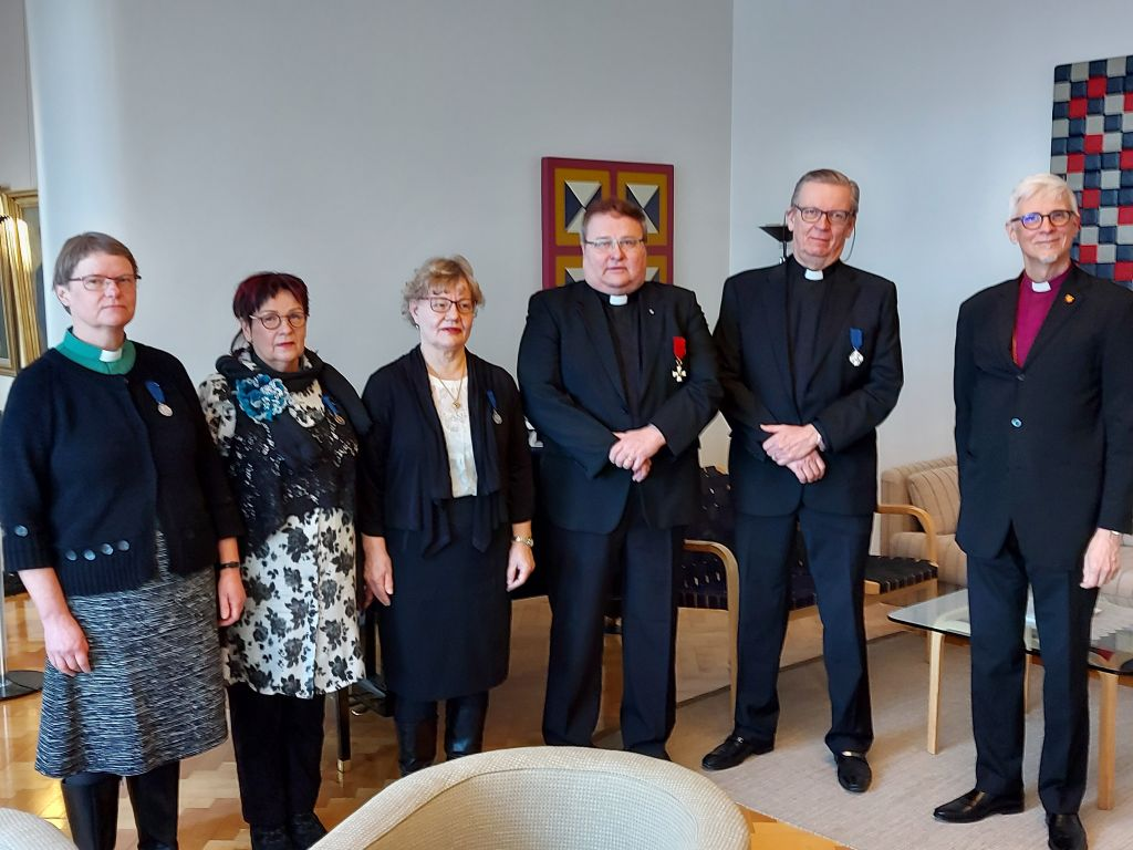 Kuvassa piispan kanssa kunniamerkkien vastaanottajia.