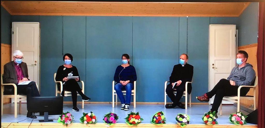 Näyttämölavalalla istuu viivsi henkilöä maskit kasvoillaan.